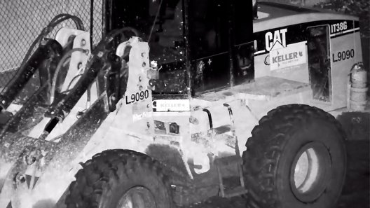 Construction equipment at night with ZLID laser illumination; text and logos are visible